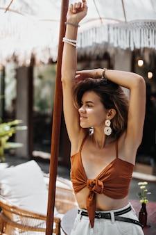 Mujer bonita en top marrón y pantalones cortos blancos sonríe afuera