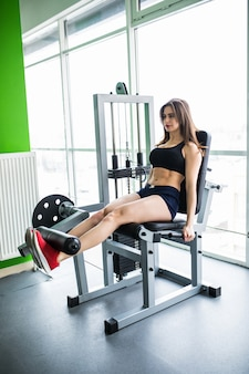 Mujer bonita trabajando sus quads en la máquina de prensa en el gimnasio.