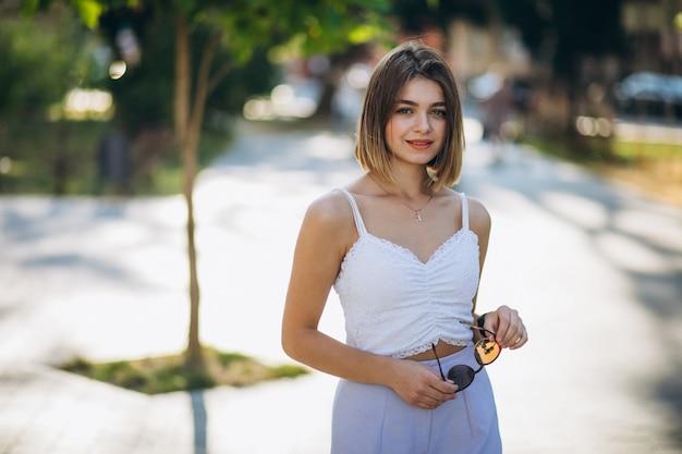Mujer bonita en traje de verano en el parque