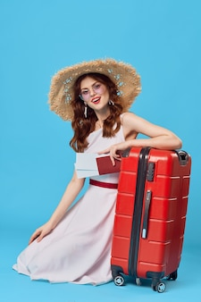 Mujer bonita turista con sombrero rojo maleta vacaciones fondo azul