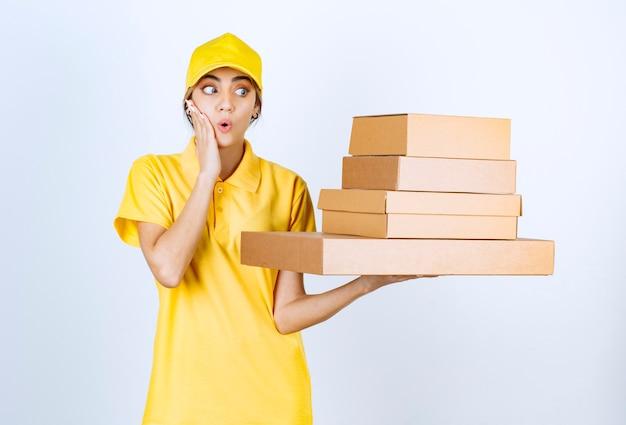 Una mujer bonita en uniforme amarillo con cajas de papel artesanal marrón en blanco.