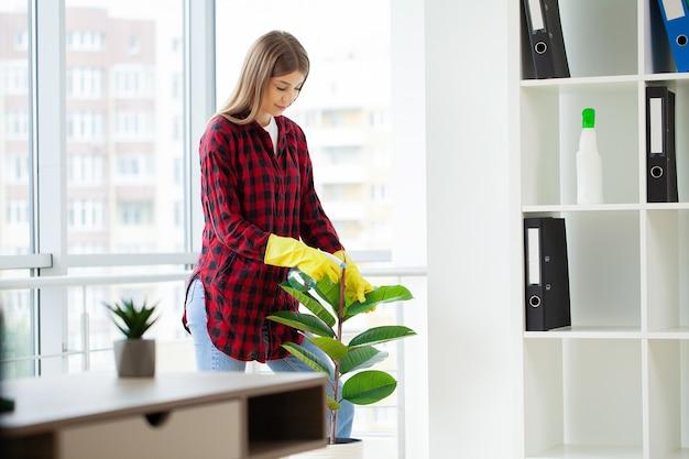 Mujer bonita en uniforme con suministros de limpieza en la oficina.