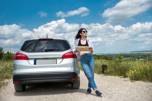 Mujer bonita ver el mapa cerca del coche en la carretera