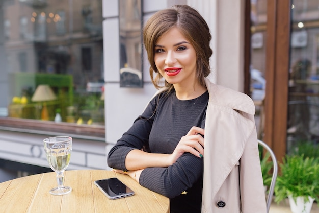 Mujer bonita vestida con vestido negro y trinchera beige con peinado elegante y labios rojos en una terraza