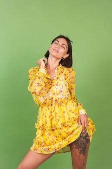 Mujer bonita en vestido amarillo de verano y gafas de sol, estudio verde, felices emociones alegres alegres positivas