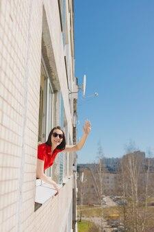 Una mujer bonita con un vestido rojo mira por la ventana de su casa una mujer se está pintando los labios