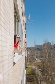 Una mujer bonita con un vestido rojo mira por la ventana de su casa