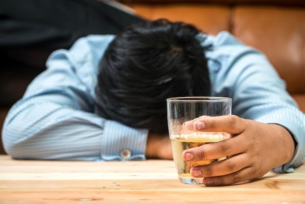 Mujer borracha sosteniendo una bebida alcohólica y durmiendo con la cabeza sobre la mesa