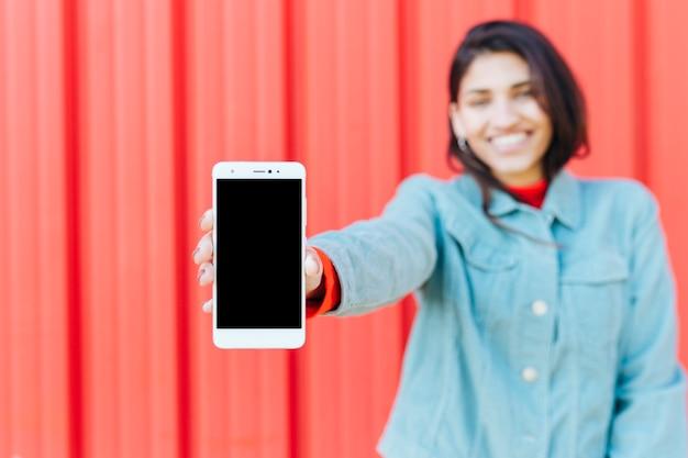 Mujer borrosa feliz que muestra el teléfono móvil contra fondo metálico rojo
