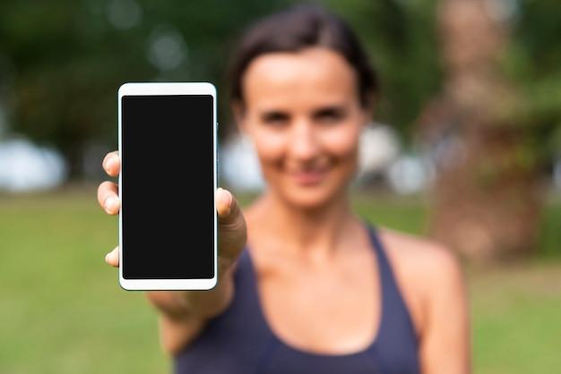 Mujer borrosa con maqueta de teléfono inteligente
