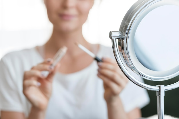 Mujer borrosa con maquillaje y espejo