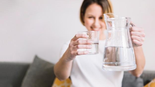 Mujer borrosa mostrando agua