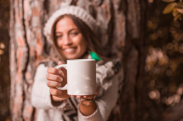 Mujer borrosa que muestra la taza cerca de un árbol