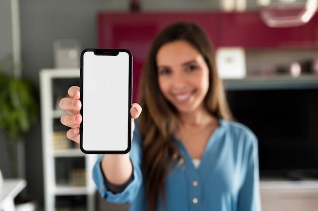 Mujer borrosa que sostiene el tiro medio del teléfono