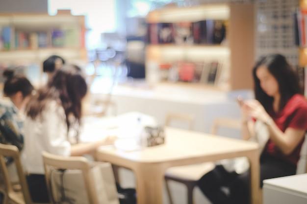 Mujer borrosa con teléfono inteligente en el fondo de la librería, personas y tecnología