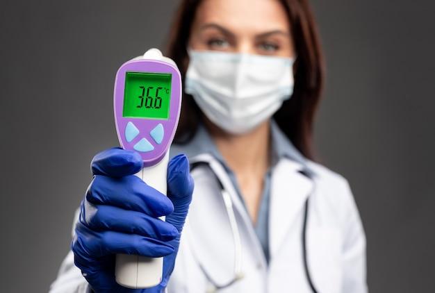 Mujer borrosa con uniforme médico y máscara que demuestra una temperatura corporal normal en la pantalla del termómetro infrarrojo durante el brote de coronavirus contra un fondo gris