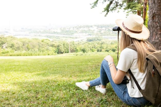 Mujer en bosque mirando a través de binoculares