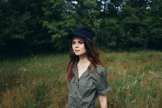 Mujer en el bosque mujer en traje verde gorra negra vista lateral estilo de vida aire fresco