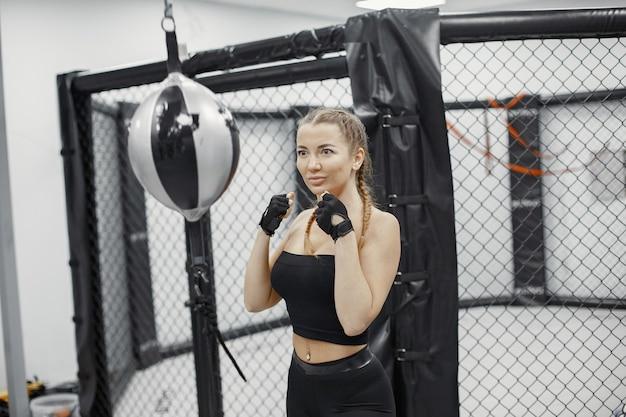 Mujer de boxeo. principiante en un gimnasio. dama en ropa deportiva negra.
