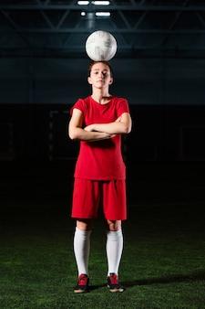 Mujer con los brazos cruzados sosteniendo la bola en la cabeza.