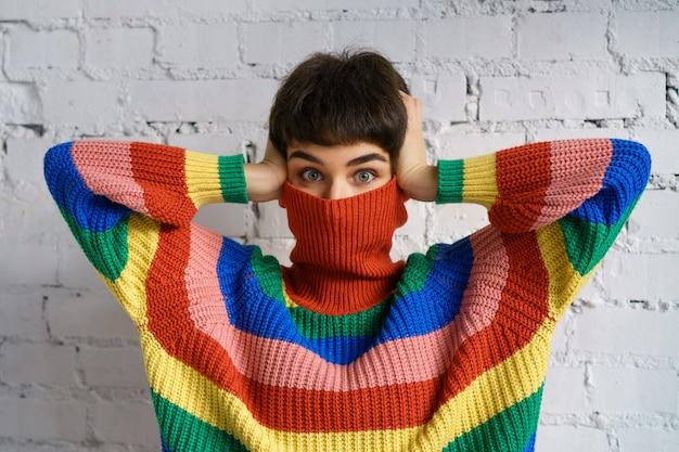 La mujer en un brillante suéter multicolor arcoiris esconde su rostro y cubre sus orejas con sus manos.