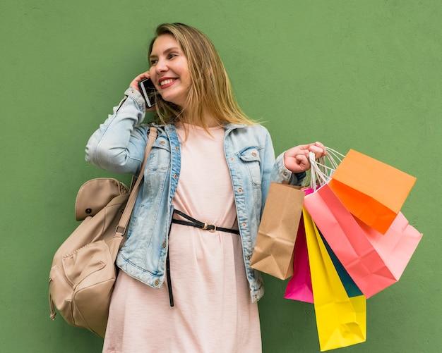 Mujer con brillantes bolsas de compras hablando por teléfono