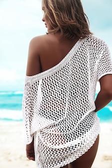 Mujer bronceada en blusa blanca transparente caminando en la playa de verano