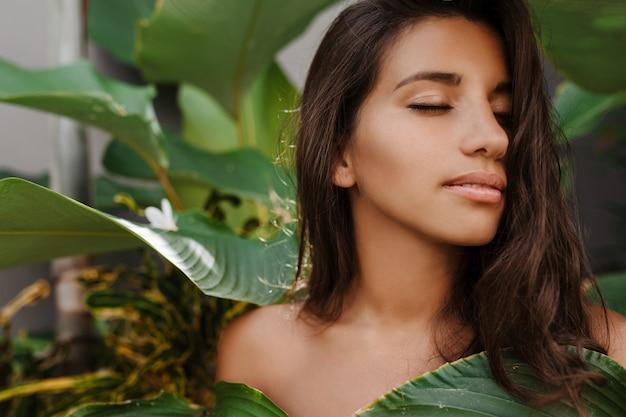 Mujer bronceada sin maquillaje posando entre plantas tropicales con hojas enormes