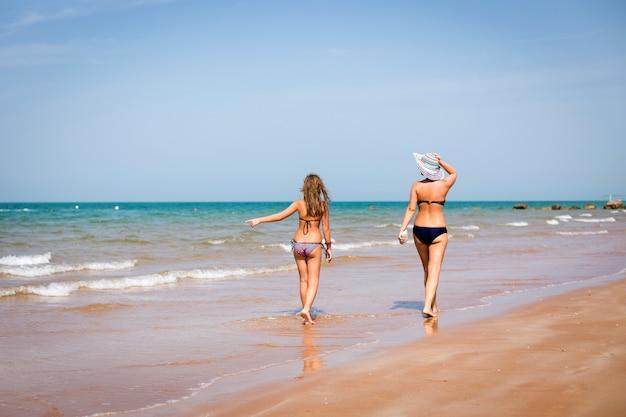 Mujer bronceada y una niña caminando por la orilla del mar
