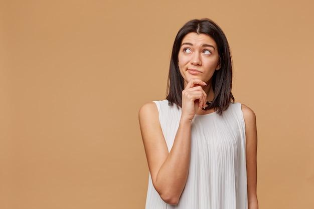 Mujer bronceada pensativa insatisfecha de pie con la mano sosteniendo la barbilla, frunciendo el ceño, mirando la esquina superior izquierda en el copyspace en blanco, expresando desconfianza y malentendido,
