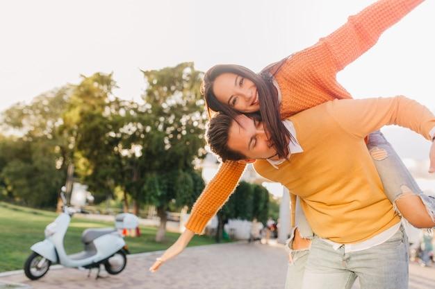 Mujer bronceada en suéter divertido posando con novio no lejos de scooter