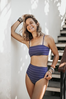Mujer bronceada en traje de baño azul oscuro riendo y mirando al frente afuera