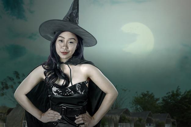 Mujer bruja asiática con un sombrero de pie con la escena nocturna