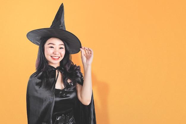 Mujer bruja asiática con un sombrero de pie