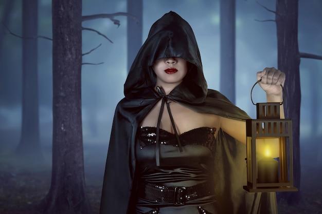 Mujer bruja asiática sosteniendo la linterna