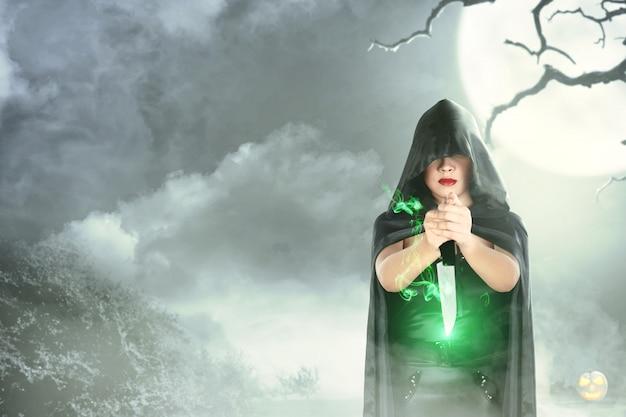Mujer bruja con capucha negra haciendo magia ritual con un cuchillo