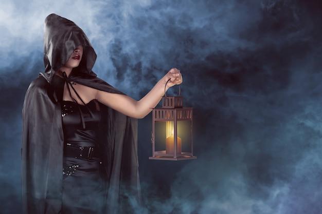 Mujer de bruja de halloween con linterna con fondo de niebla