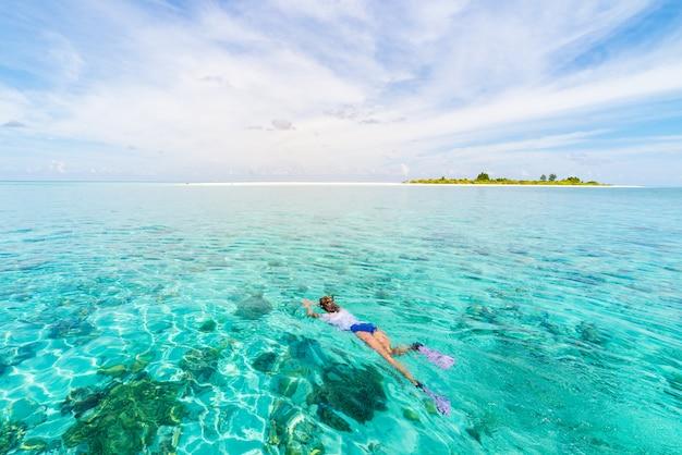 Mujer buceando en el arrecife de coral del mar caribe tropical, agua azul turquesa