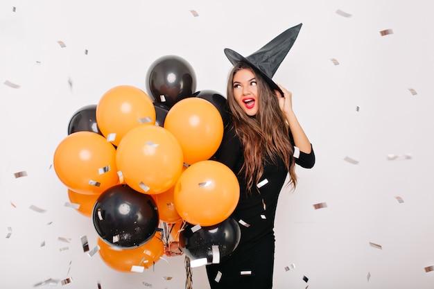 Mujer de buen humor con labios rojos posando con sombrero de carnaval
