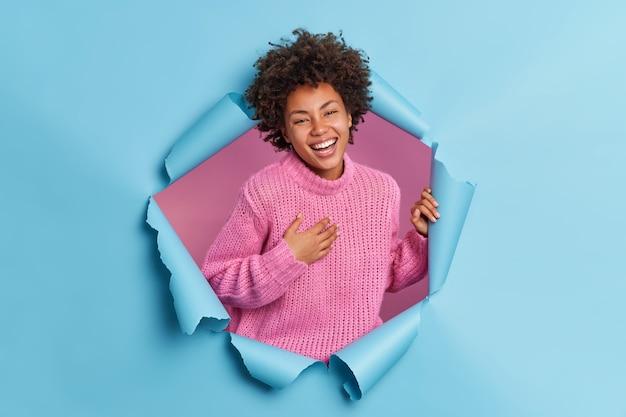 Mujer de buena apariencia positiva con cabello afro sonríe ampliamente mantiene la mano en el pecho