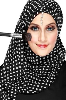 Mujer en bufanda aplicando rubor en