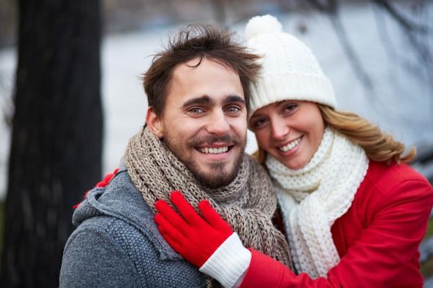 Mujer con bufanda y gorro de lana abrazando a su novio