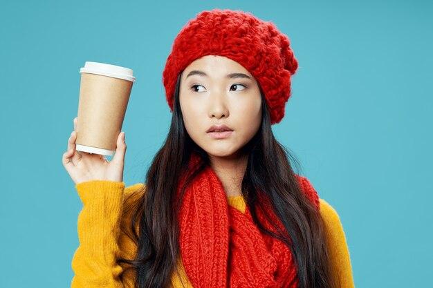 Una mujer con una bufanda roja y un sombrero con una taza de café en sus manos