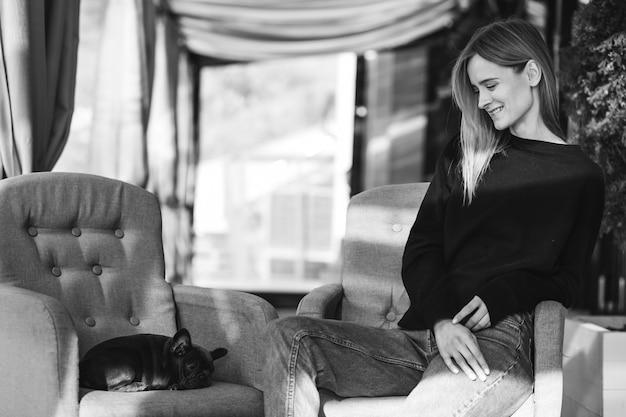 Mujer con bulldog sentado en un café