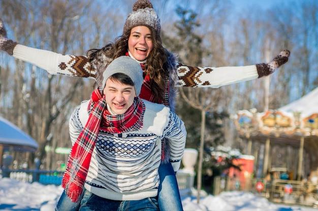 Mujer cabalga sobre la espalda de su novio en el parque de invierno. hombre dando novia caballito