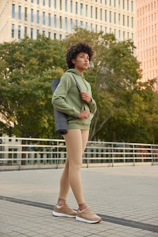 Mujer con cabello afro vestida con leggings con capucha y zapatillas de deporte tiene sesiones de entrenamiento físico regulares en ejercicios de entorno urbano al aire libre para mantenerse en forma