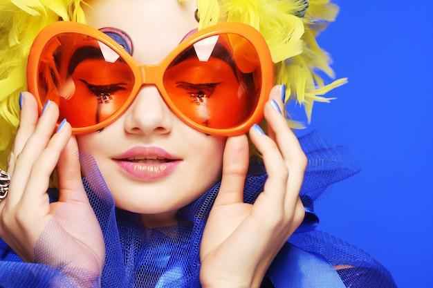 Mujer con cabello amarillo y gafas de carnaval