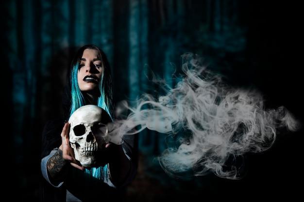 Mujer con cabello azul sosteniendo una calavera con humo