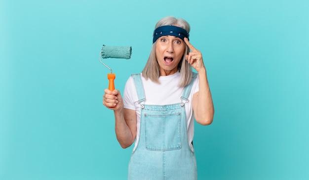 Mujer de cabello blanco de mediana edad que parece sorprendida, dándose cuenta de un nuevo pensamiento, idea o concepto con un rodillo pintando una pared