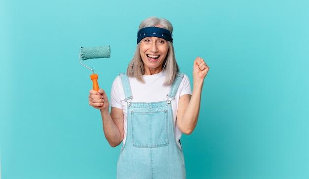 Mujer de cabello blanco de mediana edad que se siente conmocionada, riendo y celebrando el éxito con un rodillo pintando una pared